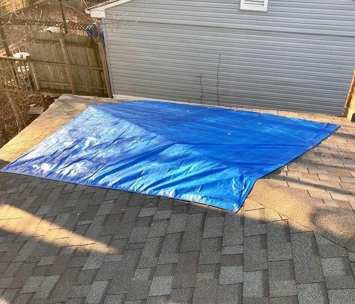 A roof of a house with a section covered by a blue tarp.