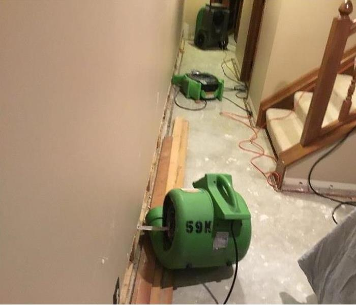 Hallway of a home with carpeting removed and two airmovers and a dehumidifier set up.