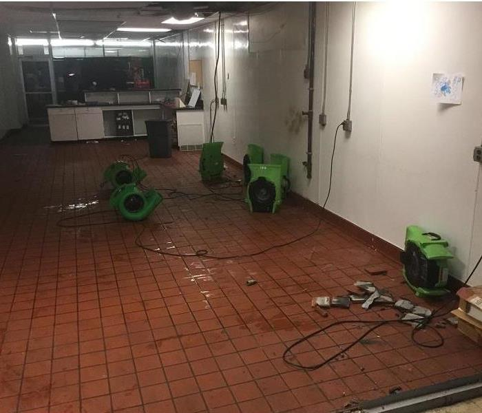 Large room with tile flooring that has water in areas throughout. Seven air movers are placed in the room.