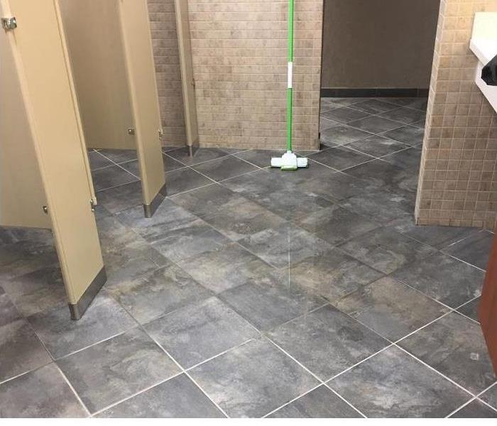 Bathroom in commercial building with tile walls and floors. Standing water on floors and mop leaning against wall.