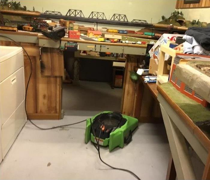 Basement room with air mover set up on floor.