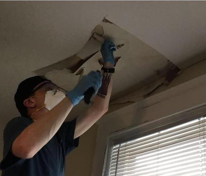 Man wearing gloves and a face mask working on a ceiling.
