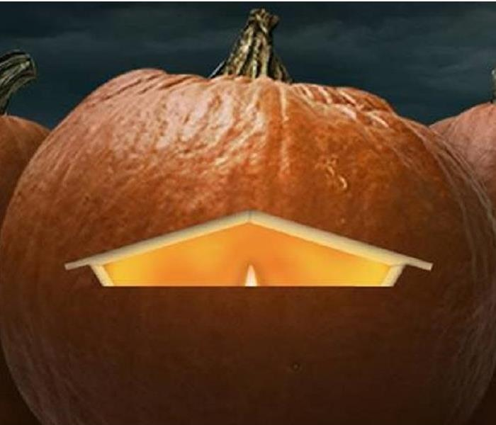 Orange pumpkin with candle seen through carving of a house shape.